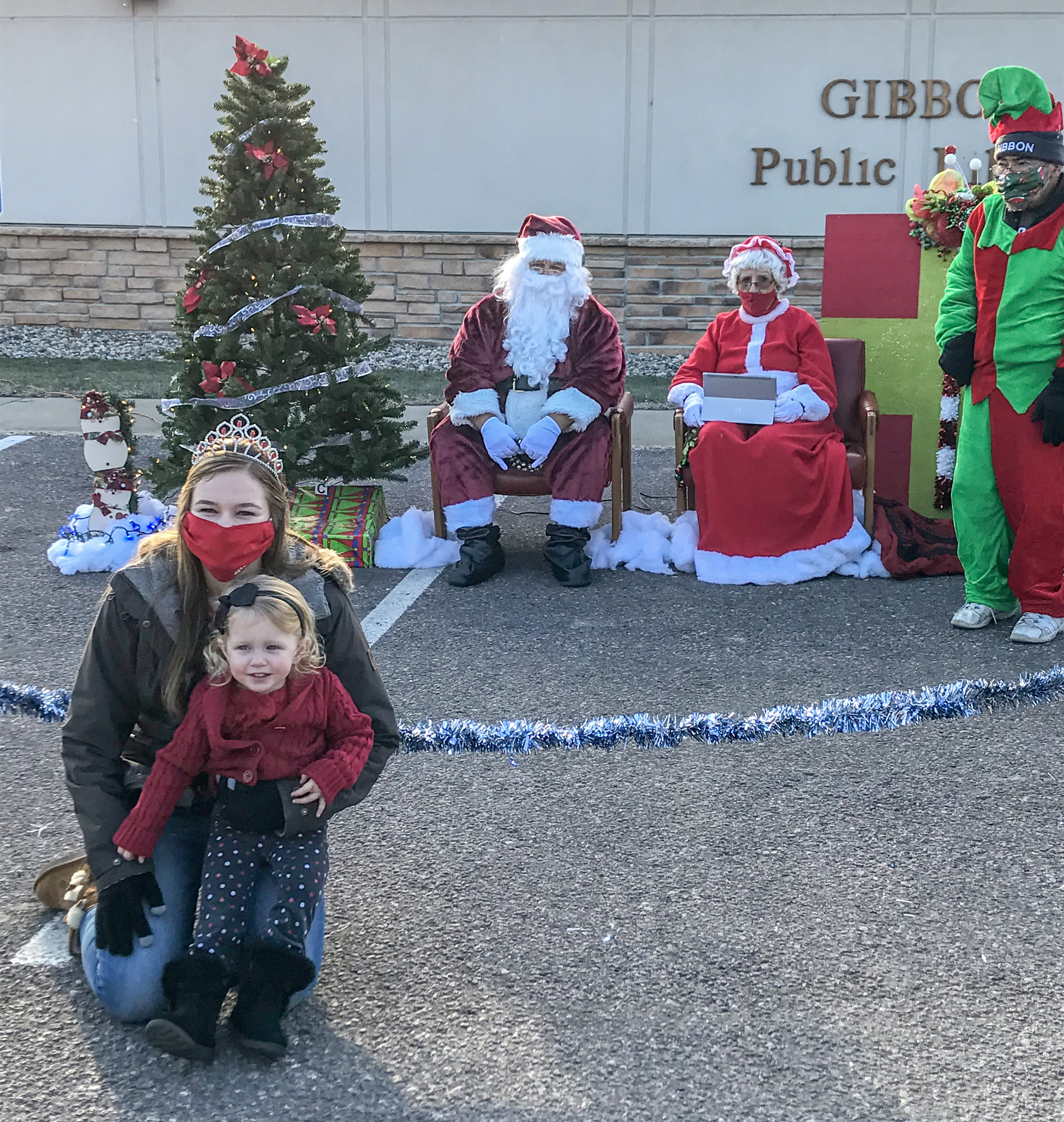 Miss Gibbon, Baleigh Peterson, poses with her little sister and Santa and Mrs. Claus.