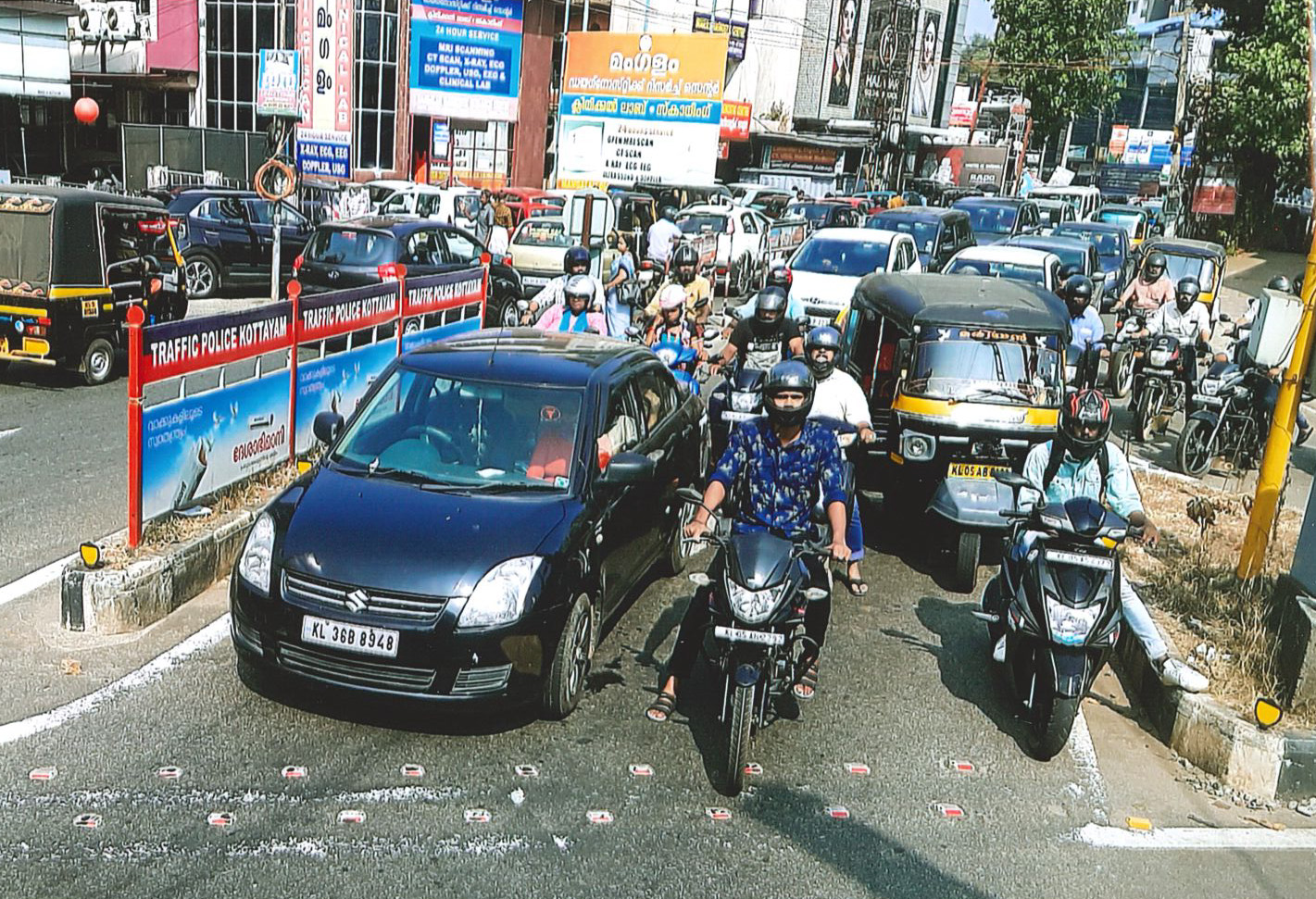 A typical two-lane road in India with cars and trucks that form two lanes, and motorcycles and scooters that fill in every available space in between, alongside, in front of and behind the rest of the traffic.