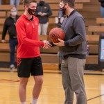 Head Coach Jon DeRock presents Damian Hopp with the game ball from the T-Birds' game against Wabasso on Monday evening.  Hopp scored his 1,000th career point during the game. (Staff photo by Denise Bonsack)