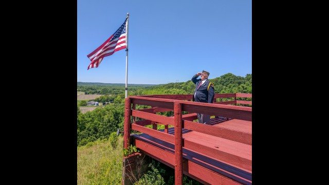 Jerry Peichel stands at attention and salutes the flag that flies proudly over the river valley at Peichel's Hill. (Submitted photo)